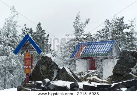 KACHKANAR, RUSSIA - JANUARY 09, 2018: gates and prayer drums in the Ural Buddhist monastery Shad Tchup Ling in the background of the winter landscape
