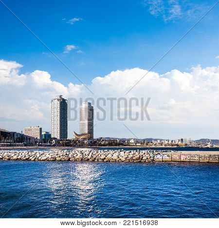 Barceloneta beach and Port Olimpic in Barcelona, Spain. Skyscrapers towering over the marina in Port Olimpic  Harbor