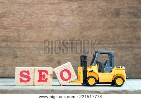 Yellow toy forklift hold letter block O to complete word SEO (Abbreviation of search engine optimization) on wood background
