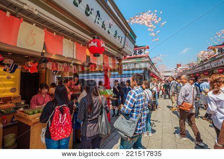 Tokyo, Japan - April 19, 2017: crowd of tourists while shopping souvenirs and traditional Japanese food on Nakamise-dori, at Senso-ji Temple, Asakusa. Cherry blossoms season.