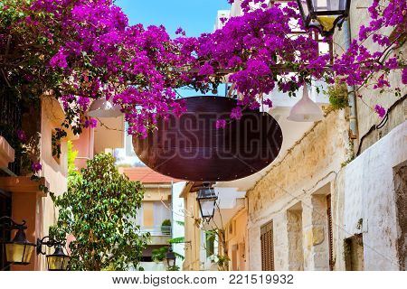 Decorated street advertising signboard on narrow touristic street in tourist routes. Walk around old resort town Rethymno in Greece. Mediterranean architecture on Crete