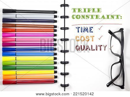 Project Management Triple constraint text on white sketchbook with color pen and eye glasses, Top View/Flat Lay