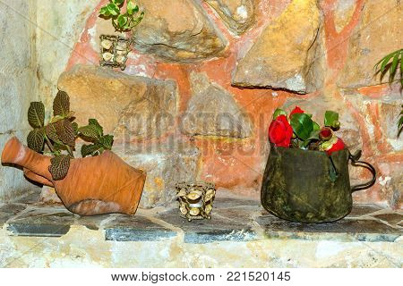Old tin mug and a chipped clay jug decorated with flowers and plants on the background of an old stone wall made of granite boulders. Resort town Rethymno in Greece. Mediterranean culture on Crete