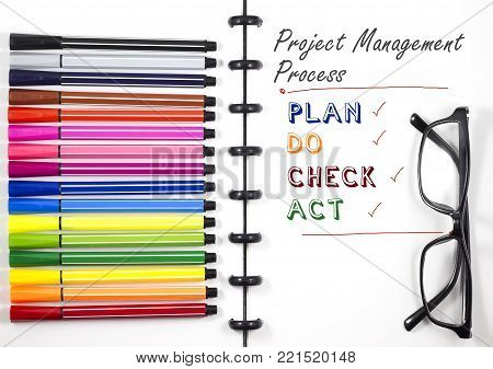 Project Management Process text on white sketchbook with color pen and eye glasses, Top View/Flat Lay