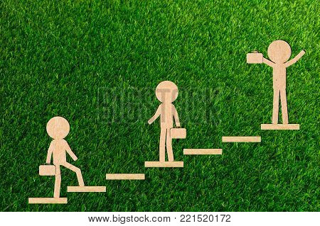 Walking Business concept teamwork the stairs walks up to the goal to succeed paper cut of a green background