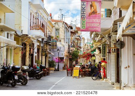 Rethymno, Greece - May 3, 2016: Tourists eat at tables in street cafe with national cuisine. Street advertising signboard on touristic street. Mediterranean architecture and cuisine on Crete