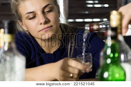 lonely sad woman drinks alcohol in bar, lot of empty bottles around her. social issue concept, female alcoholism.