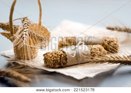 two muesli bars in parchment wrapper with wheat ear in the wattled basket on backing parchment background
