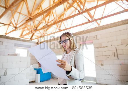 Beautiful young architect looking at blueprints, controlling issues at the construction site.