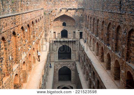 NEW DELHI, INDIA - CIRCA NOVEMBER 2017: Underground step-well Ugrasen ki Baoli in heart of New Delhi, India. 14th Century AD. It is a protected monument and built by Maharaja Agrasen in the Mahabharat era.