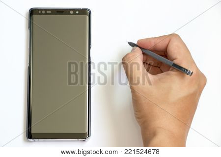 BANGKOK, THAILAND - December 23, 2017 : Business man hold the stylus to write at Samsung Galaxy Note 8 on white background. It is the flagship smartphone with android os.