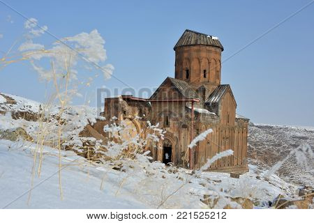 Ruins of famous  Saint Gregory (Tigran Honents) church against winter landscape background. Ani is a ruined medieval Armenian city-site situated in Turkey near border with Armenia.