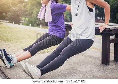 Two attractive young muscular women, Athletic woman doing some stretching push-up workout exercises warm up fitness.