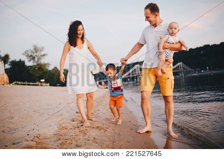 concept family beach vacation. A family of four mum, father holding his son, parents holding a child's hand walking, wanting barefoot on the river bank by the hand at sunset in the summer