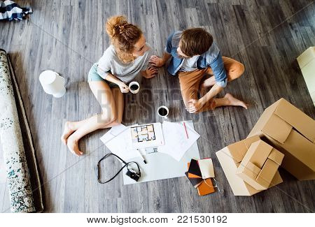 Young married couple moving in new house, sitting on the floor near cardboard boxes, drinking coffee.