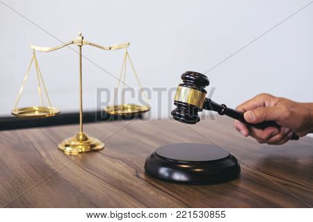 Male lawyer or judge working with Law book, gavel, report the case on table in modern office, Law and justice concept.