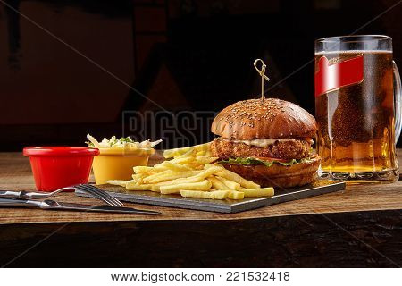 Tasty burger, french fries with sauce and glass of beer on black board. Still life. Served at restaurant, cafe, bar, pub cheesburger, hamburger