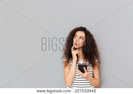 Picture of nice woman touching her lips and looking aside while thinking about something important or trying to remember, over grey background