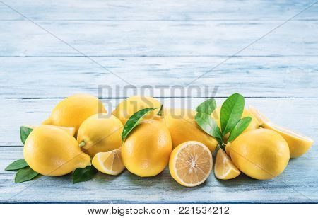 Ripe lemons and lemon leaves on blue wooden background. Top view.