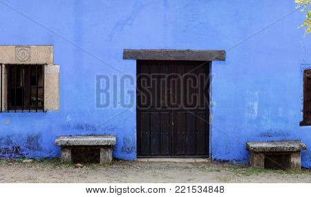 Blue Facade of old house with windows and wooden door. Cáceres, Spain.