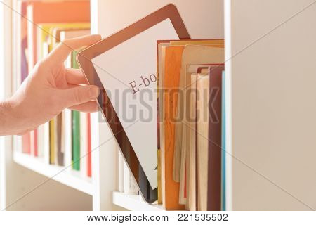 Man taking modern ebook reader from a bookshelf.