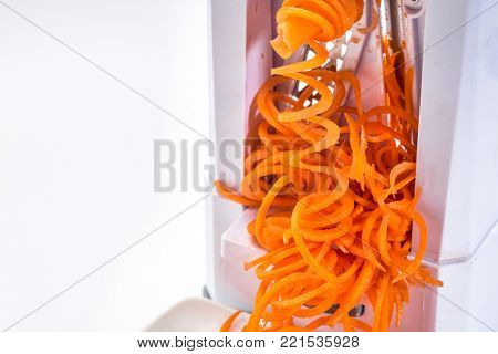 fresh raw carrot being processed with spiralizer (spiral slicer)