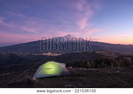 illuminated tent on mountain of Nebrodi Park at the twilight, on background lights of town under Etna Volcano, Sicily