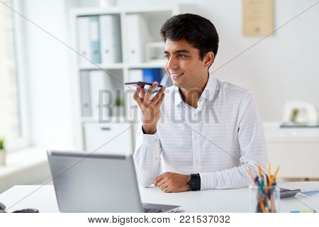 business, people and technology concept - businessman with laptop computer using voice command recorder on smartphone at office