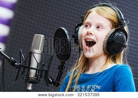 Regording studio. Child girl singing or role voicing