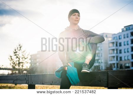 Full length of a beautiful young woman looking at camera, with a confident smile while tying the shoelaces of her sport shoes outdoors in the park