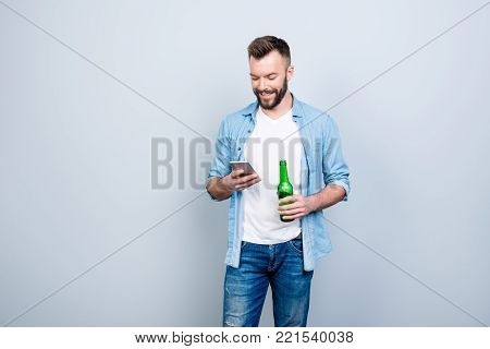 Happy Joyful Cheerful Bachelor Is Drinking Beer And Using Smartphone For Typing Sms, Isolated On Gre
