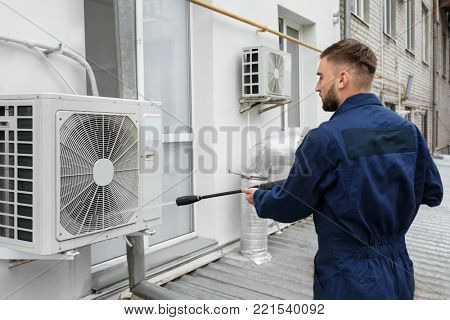 Male technician cleaning air conditioner outdoors