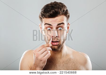 Terrified man removing nose hair with tweezers isolated over gray background
