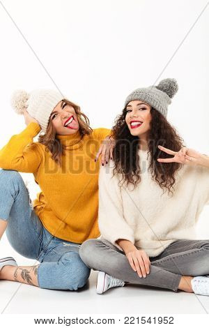 Vertical image of Two funny girls in sweaters and hats sitting on the floor together while having fun and looking at the camra over white background