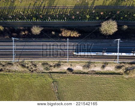 High speed electric passenger train in countryside overhead aerial view