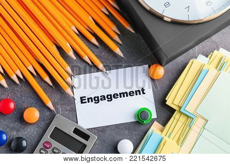 Composition with paper, pencils, calculator, clock and word ENGAGEMENT on table