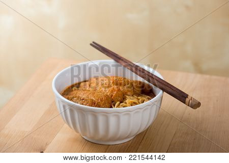 Curry laksa with chopsticks, a popular spicy dish in Malaysia cuisine.