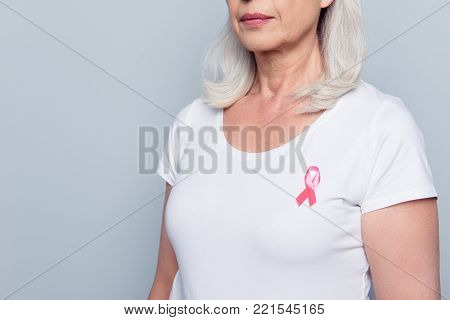 Cropped close up portrait of half turned aged woman in white t-shirt with breast cancer pink ribbon and serious expression over grey background