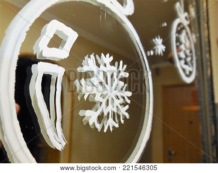 Two Christmas tree decorations in the form of balls with a snowflake and a Christmas tree on the center are painted with white paint on the mirror