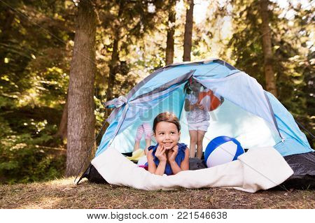 Two beautiful little girls with colorful beach balls sitting in tent, camping by the lake.