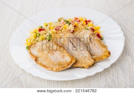 Fried pork schnitzel with vegetable mix in white plate on wooden table