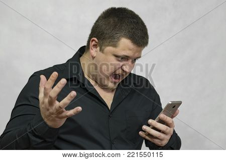A angry man with a phone in his hand. He is outraged by the sudden disconnection of the mobile phone and swears aloud.