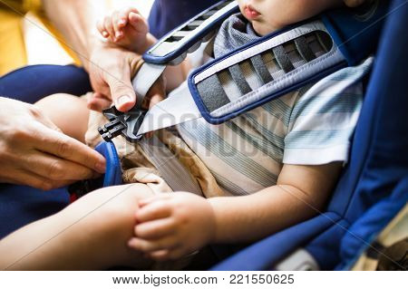 Unrecognizable father fastening seat belt for his son sitting in safety seat in the car.