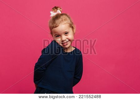 Shy young blonde girl posing in studio and looking at the camera over pink background