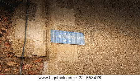 ORADOUR SUR GLANE, FRANCE - December 03, 2017 : on the wall of a house destroyed during the massacre by the Nazis of the population on June 10, 1944, a blue street plaque where it is written - street Emile DESOURTEAUX 1842 - 1906