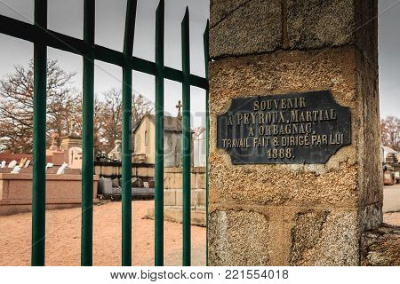 ORADOUR SUR GLANE, FRANCE - December 03, 2017 : commemorative plaque at the entrance of the cemetery where it is written in French - souvenir to PEYROUX Martial in ORBAGNAC work done and directed by him 1888