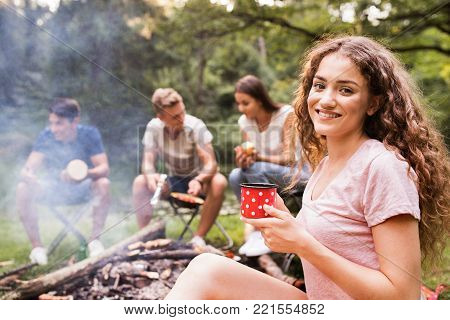 Beautiful teenage girl with her friends enjoying camping vacations in forest. Boys cooking meat on bonfire.