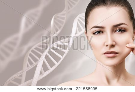 Portrait of sensual woman pulling cheek in DNA chains. Over beige background.