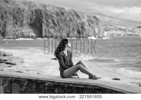 Pretty girl or beautiful woman, sexy slim brunette, sitting on stone wall on on sunny summer day outdoors on blue stormy sea background