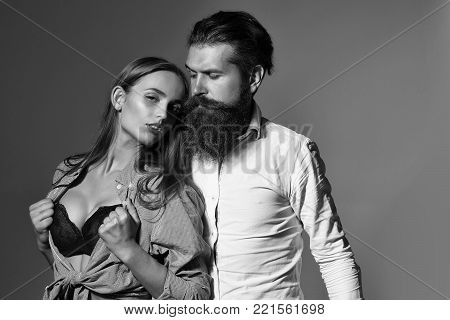 Young sexy couple of bearded handsome man hipster with beard and moustache and pretty girl or beautiful woman in red sexi bra in unbutton shirt on grey wall